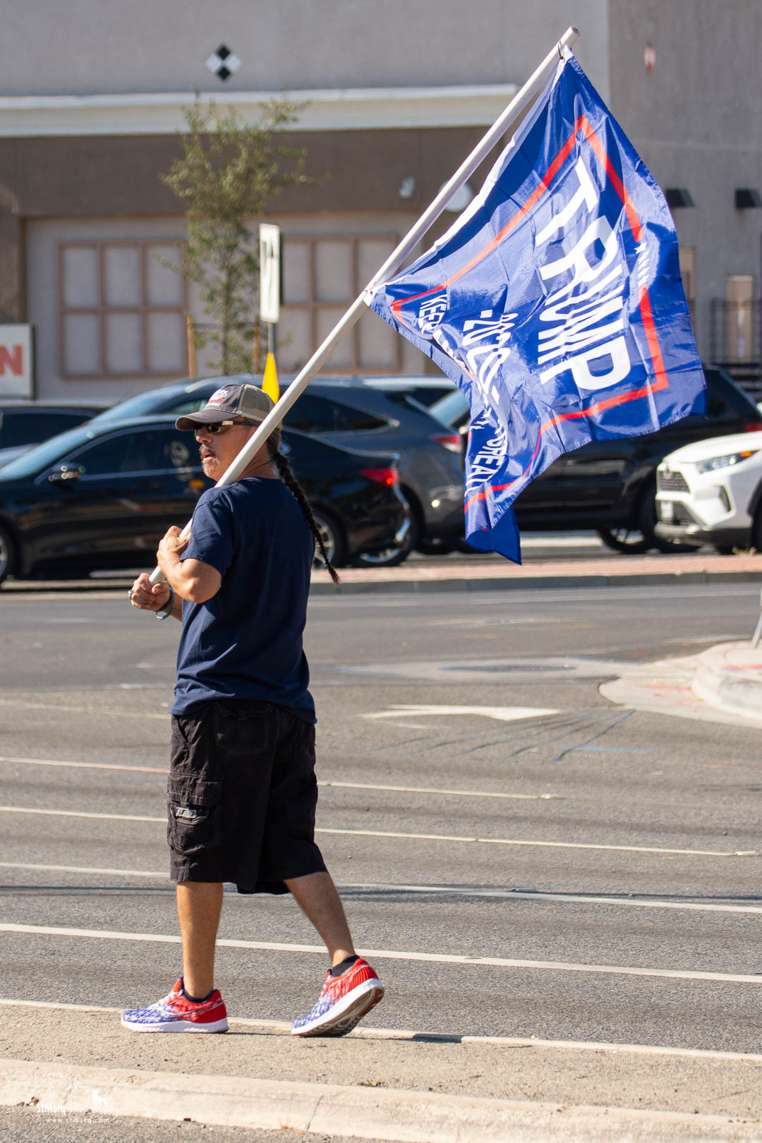 Fernando Castillo walks in the center divider of Imperial Highway with a Trump flag on Sunday, October 18, 2020 at a Rally in support of president Trump in La Habra, California.